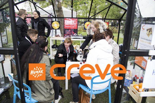Ihmisiä taustalla, etualalalla Creven logo.