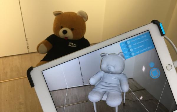 Kuvassa taustalla pehmonalle ja edessä Ipad. Ipadin ruudulla 3D-mittaamalla tuotettu 3D-malli nallesta.
