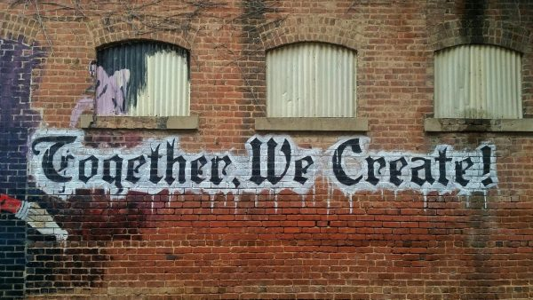 A brick wall, marked with a graffiti that says ''Together We Create!''